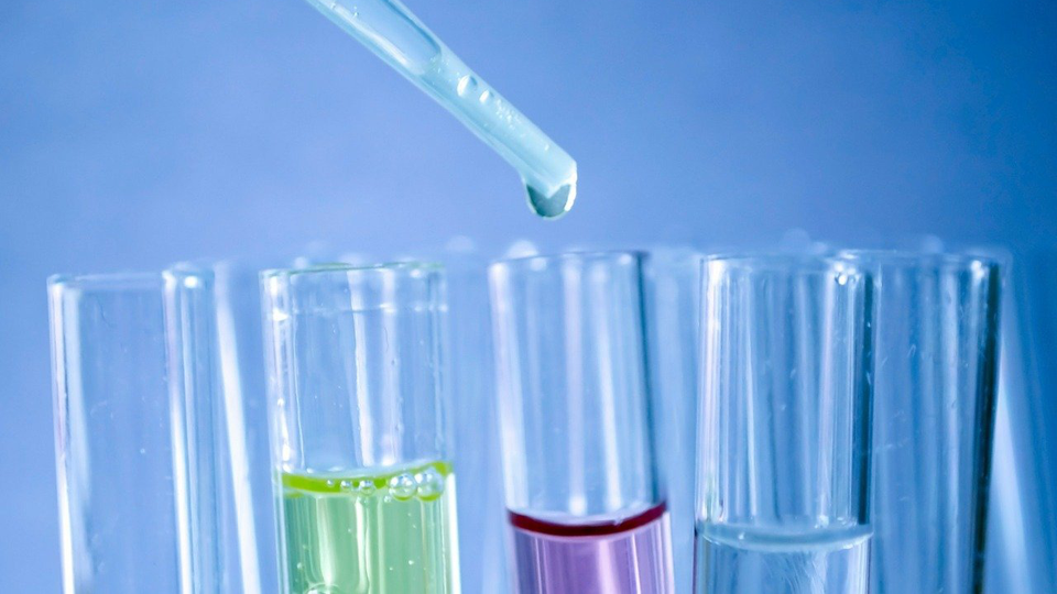 Test tubes being filled with coloured fluids by a pipette